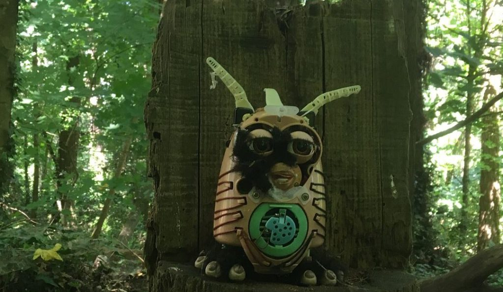 A mutilated Furby sits on an altar-like stump in the woods...